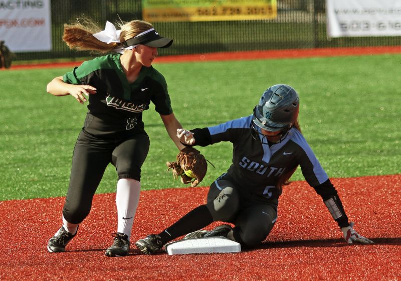 PMG PHOTO: DAN BROOD - Tigard junior second baseman Abby Soderquist (left) looks to put a tag on South Salem junior Makenna McCool during Monday's state playoff game.