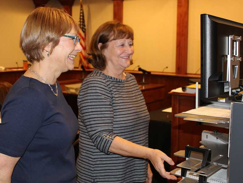 HOLLY M. GILL - Jefferson County Clerk Kate Zemke, left, and volunteer Lynn Weisen run some of the last ballots through the vote counting machine Tuesday night.