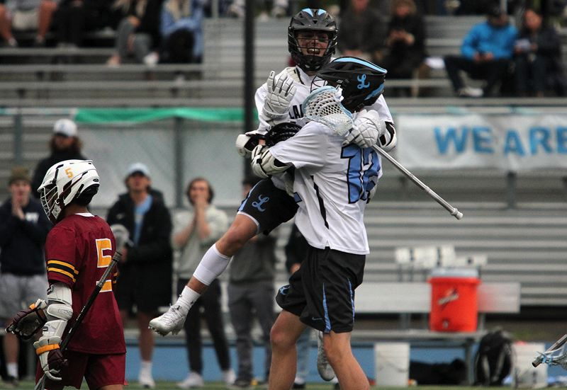 PMG PHOTO: MILES VANCE - Lakeridge's Ty DeLancellotti gets lifted into the air by teammate Thiago Achar-Winkels during his team's 13-5 win over Central Catholic in the OHSLA state playoffs at Lakeridge High School on Tuesday, May 21.