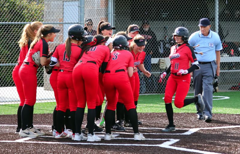 PMG PHOTO: JIM BESEDA - Clackamas' Shay Monise (11) is greeted at home plate by her teammates after he two-run homer in the third inning gave the Cavaliers a 3-0 lead in Monday's playoff game against Roosevelt.