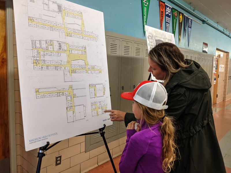 PMG PHOTO: COURTNEY VAUGHN - Tracy Bowles and daughter Ryan, 8, check out site design plans for a remodel project at Madison High School.