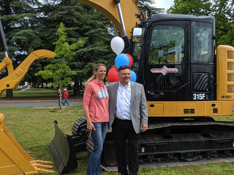PMG PHOTO: COURTNEY VAUGHN - Madison High School Principal Petra Callin and Portland Public Schools Superintendent Guadalupe Guerrero pose in front of construction equipment at Madison High School during a groundbreaking ceremony Saturday, May 18.