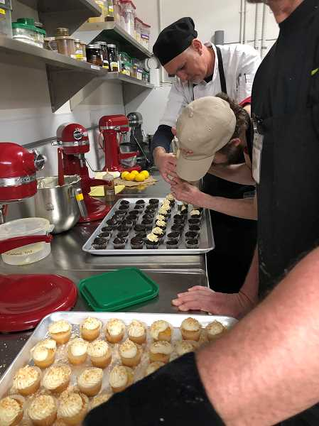 Bakers put the finishing touches on freshly baked cupcakes with the help of professional pastry chef Daniel Farris, furthest from the camera.