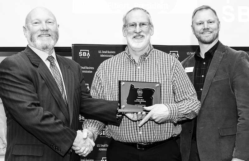 SUBMITTED PHOTO - A.R.E. Manufacturing President Alvin Elbert was recently recognized as the 2019 Small Business Administration Portland District Small Business Champion for efforts in starting up Tiger Manufacturing, the machine shop run by students at Newberg High School. Pictured at center is Elbert, while pictured at left is SBA Portland District Director Martin Golden and right is SBA Regional Administrator Jeremy Field.