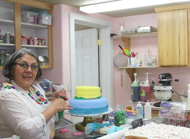 DESIREE BERGSTROM/MADRAS PIONEER - Yara Santos stands by a couple of her cakes at her cake shop's location at 123 SW H St. in Madras. She started making cakes for friends and family for free, then doing orders out of her home. But after 15 years of making cakes for people, she and her husband have opened a business with a storefront.