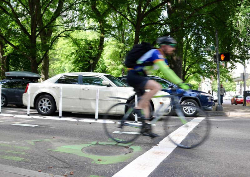 PMG PHOTO: ZANE SPARLING - A cyclist zips down Southwest Madison Street toward the Hawthorne Bridge on Monday, May 20.