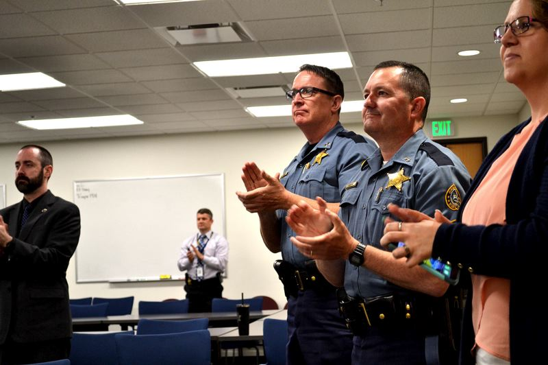 OREGON CAPITAL BUREAU: AUBREY WIEBER - Capt. Tim Fox, center left, and Superintendent Travis Hampton stand and clap as Trooper Nic Cederberg is awarded the Medal of Valor from President  Trump Wednesday, May 22.