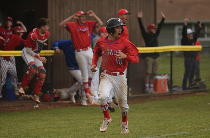 PMG PHOTO: DAVID BALL - Pinch-runner John McQuillin trots home while the La Salle dugout erupts after seeing Matt Evans grand slam clear the fence to put the Falcons in front in the fifth inning of their 8-7 playoff win over Ashland on Wednesday.