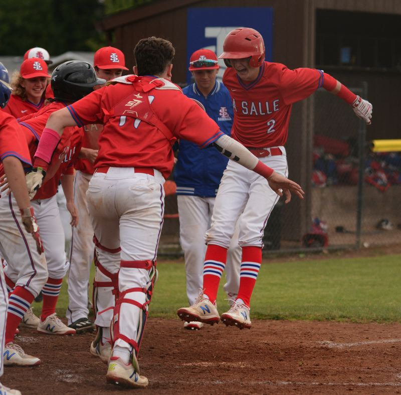 PMG PHOTO: DAVID BALL - La Salle Preps Matt Evans jumps onto home plate after his grand slam in the fifth inning to put the Falcons on top 8-5.