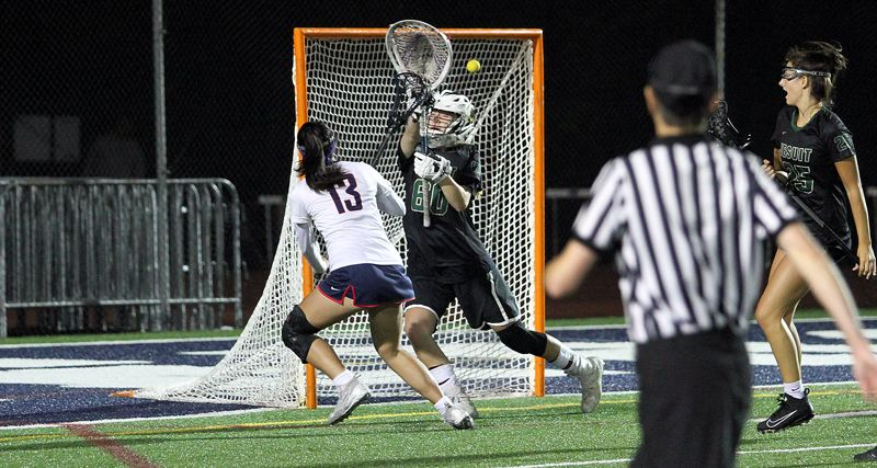 PMG PHOTO: MILES VANCE - Lake Oswego's Rylee Sutherland beats Jesuit goalie Nina Mahler with what appears to be a game-tying goal in the final seconds of the OGLA state championship game at Lake Oswego High Shool on Thursday, May 23. But game officials ruled that Sutherland's score had come after time experied, leaving Jesuit with a 13-12 victory and its first state title.