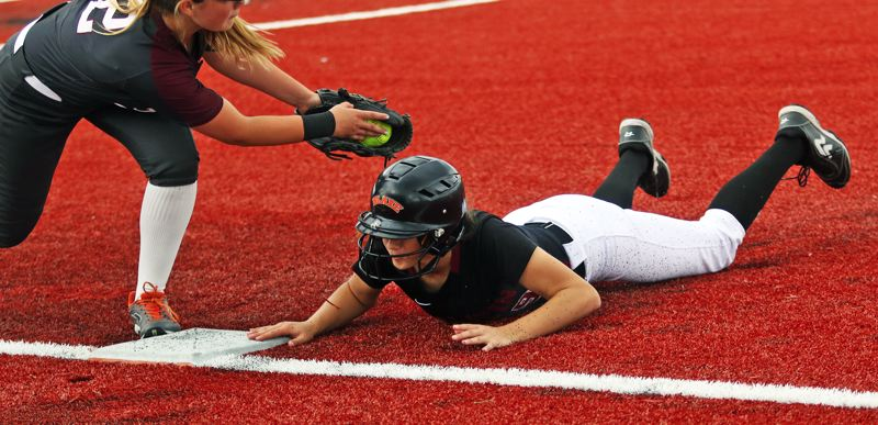 PMG PHOTO: DAN BROOD - Tualatin High School junior Sydney Wagner dives back to first base on a pickoff play during the Timberwolves' 2-0 playoff win over Franklin.
