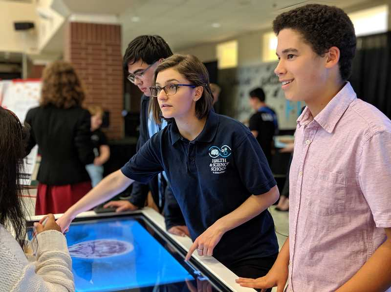 PMG PHOTO: COURTNEY VAUGHN - Aubrianna Littier, a senior at the Health & Science School, shows off a digital autopsy table during iX19. To the right, student Caden Rinell helps answer questions.