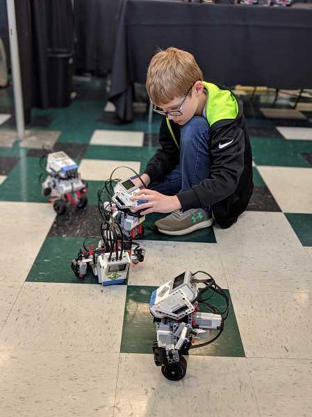 PMG PHOTO: COURTNEY VAUGHN - Eric Demcak watches a flurry of robots march around a booth during an iX19 Innovation Expo at Aloha High School.
