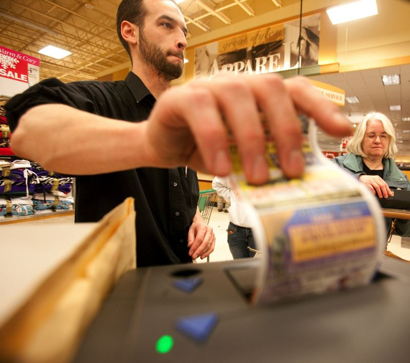 FILE PHOTO - A cashier pulls a receipt from his register for a customer at a local store.