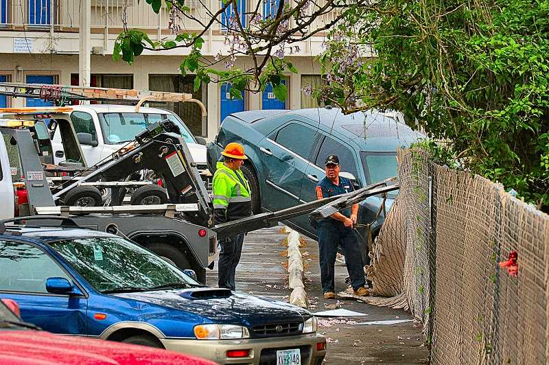 DAVID F. ASHTON - After hours of struggle involving two tow trucks, the carjacked and crashed Chrysler was finally yanked back through the fence on S.E. Powell Boulevard.