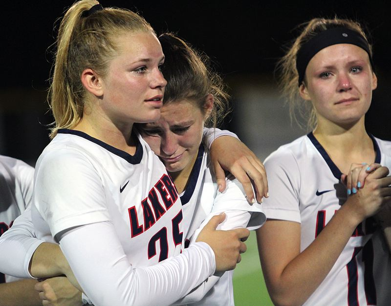 PMG PHOTO: MILES VANCE - Lake Oswego's (from left) Zoe Ziegler, McKinley Mullen and Riley Kennon can't hide their emotions following their team's 13-12 loss to Jesuit in the OGLA state championship game at Lake Oswego High School on Thursday, May 25.