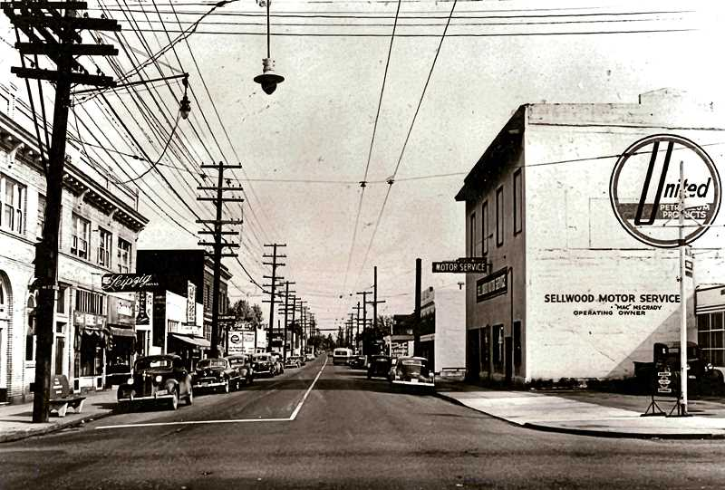 COURTESY OF SMILE HISTORY COMMITTEE - Heres S.E. 13th Avenue, looking north from Tacoma Street, in the 1940s. Sellwood Motor Service was where Starbucks is now. The Leipzig, on the left, had moved to this, its second location, by then, and was a popular lunch café. The Griessen Building is the third building on the left, just down from the Leipzig Café. The streetcar was no longer running down 13th Avenue, but in the 40s electric buses were still running there, as the overhead wires attest.