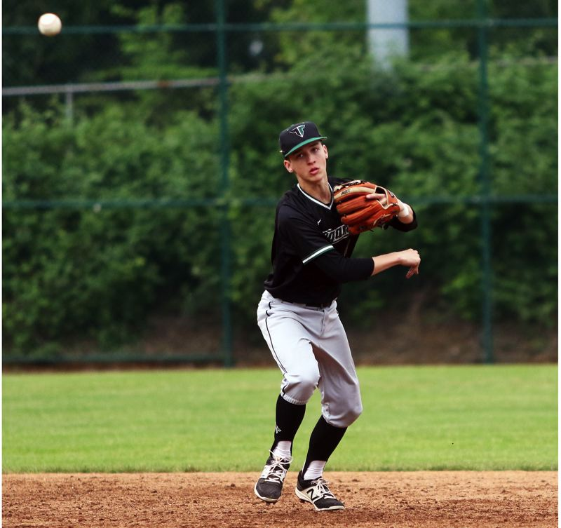 PMG PHOTO: DAN BROOD - Tigard High School junior shortstop Ethan Clark makes a throw to first base during the Tigers' state playoff game at Lakeridge.