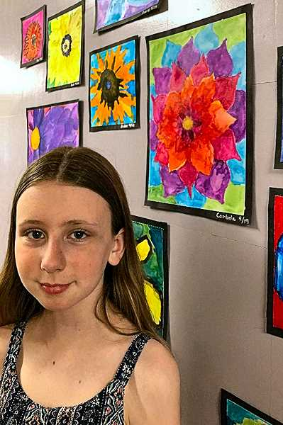 COURTESY OF AIMEE OWENS - Cambria Owens, a fifth grader art docent at Lewis Elementary School (who herself rather resembles da Vincis Mona Lisa), stands beside her red, purple, and blue flower rendering. The students studied the famous flower painter Georgia OKeefe, and drew in her style.