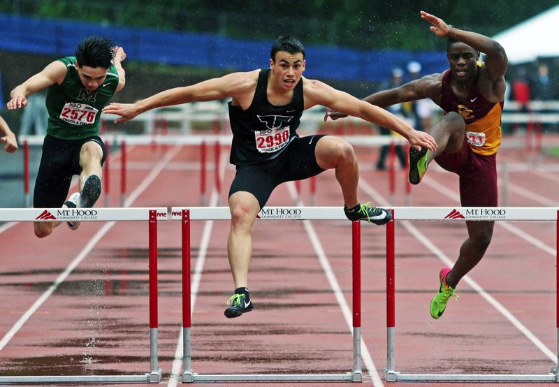 PMG PHOTO: DAN BROOD - Tigard High School junior Hunter Gilbert (center) clears the final hurdle on his way to a second-place finish in the 300-meter intermediate hurdles event at the Class 6A state meet.