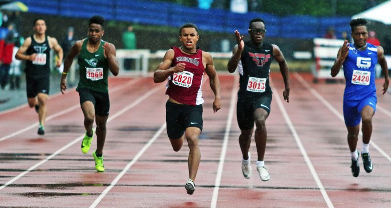 PMG PHOTO: DAN BROOD - Sherwood High School senior Caleb Hagan (center) is on his way to victory in the 200-meter dash at the Class 6A state track and field championships.