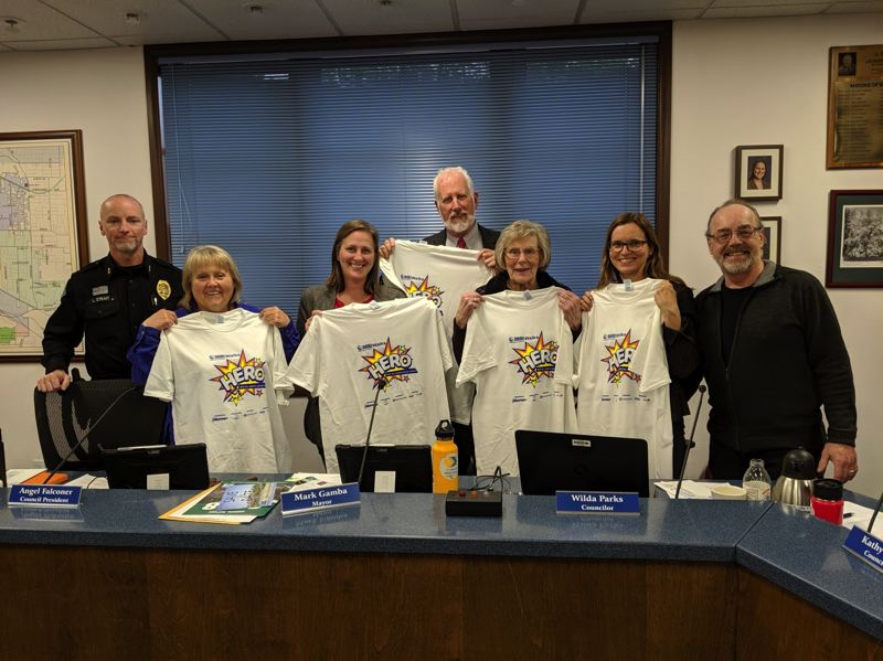 COURTESY PHOTO - Milwaukie Police Chief Luke Strait (from left), Councilor Lisa Batey, Councilor Angel Falconer, Mayor Mark Gamba, Councilor Wilda Parks and Councilor Kathy Hyzy are presented commemorative T-shirts by Gary Marschke of the Clackamas chapter of the National Alliance on Mental Illness.