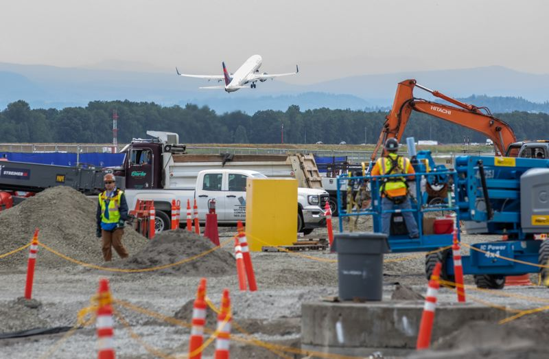 PAMPLIN MEDIA GROUP: JONTHAN HOUSE - Work on the new expanded Concourse E at PDX happens close to the runway. All workers must pass an FBI check and adhere to the Port of Portlands security and safety rules. T
