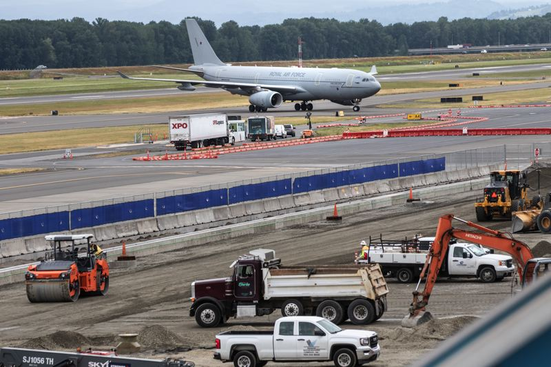PAMPLIN MEDIA GROUP: JONTHAN HOUSE - Work on the new expanded Concourse E at PDX happens close to the runway. All workers must pass an FBI check and adhere to the Port of Portlands security and safety rules.