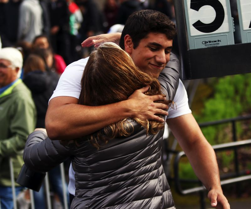 PMG PHOTO: DAN BROOD - Tualatin High School senior Nano Kis gets a hug from him mother, Claudia, following his victory in the shot put event at the Class 6A state championships.