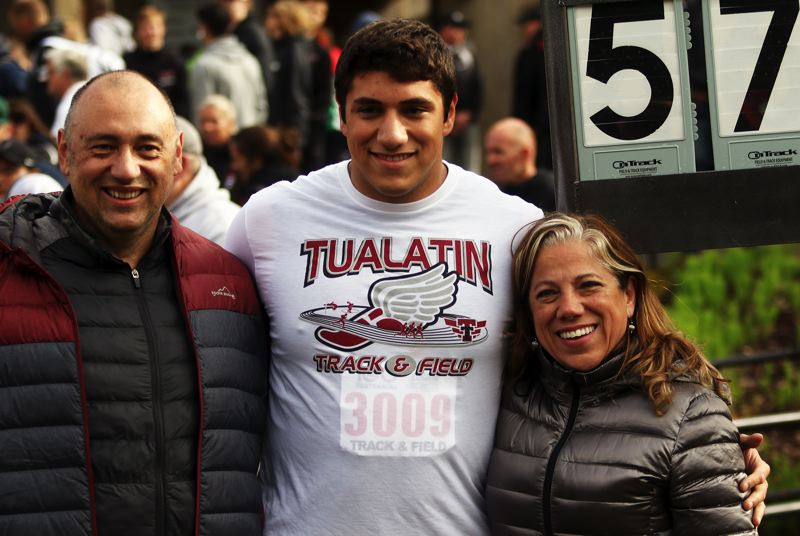PMG PHOTO: DAN BROOD - Tualatin High School senior Nano Kis smiles with his parents, Juan and Claudia Kis, following his state championship in the shot put event.