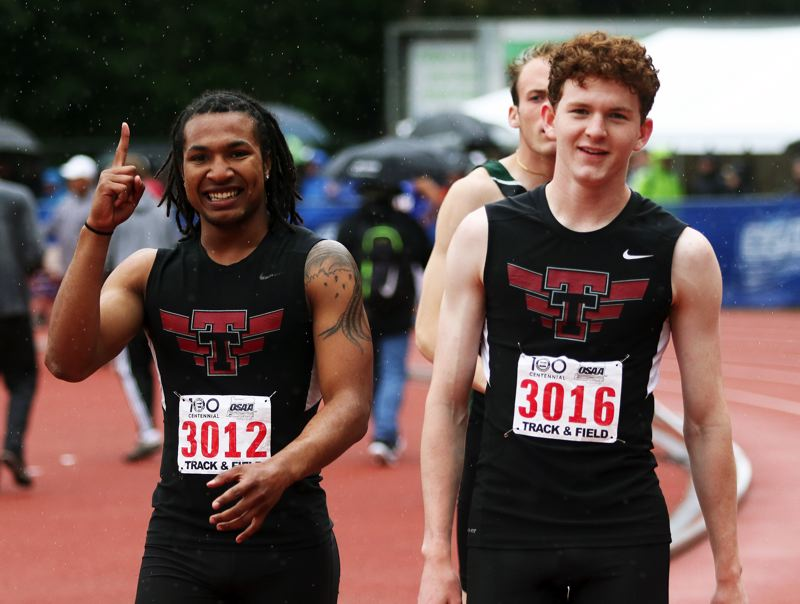 PMG PHOTO: DAN BROOD - Tualatin High School senior Dominique Loggins (left) and junior Andrew McDade are all smiles following the Wolves' winning performance in the 4 x 100 relay.
