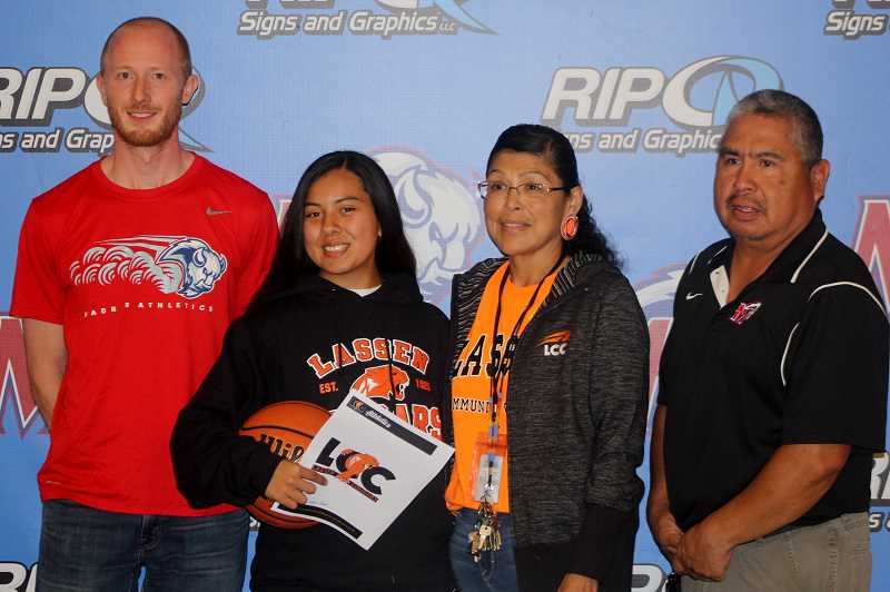 STEELE HAUGEN - Jackie Zamora-Heath signs her letter of intent to Lassen Community College in Susanville, California, next to head girls coach Jerin Say (left), mother Lisa Lomas (right) and assistant girls JV coach Butch David (far right).