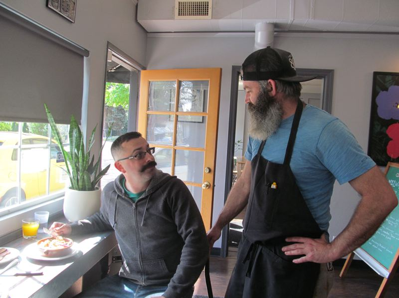 PMG PHOTO: ELLEN SPITALERI  - Right, Shea Pirtle, owner of the Milwaukie Cafe and Bottle Shop, chats with customer Ryan Brentley, who said his brisket with baked eggs was a burst on the palate.