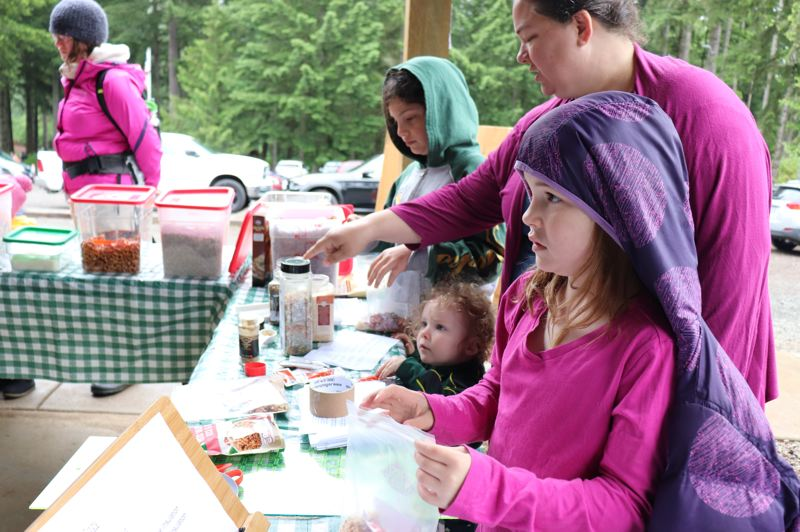 Families assemble dry ingredients for a rice-and-bean meal that they can make with a warm pouch on the trail.