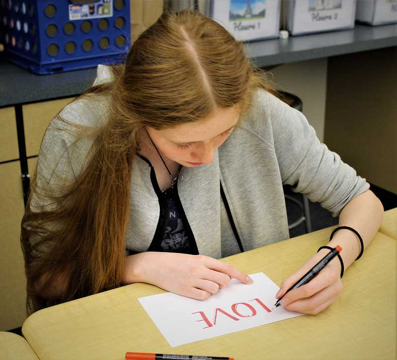 COURTESY PHOTO: KALEIGH HENDERSON - Freshman Kenna Jones writes a positive word during the calligraphy workshop.