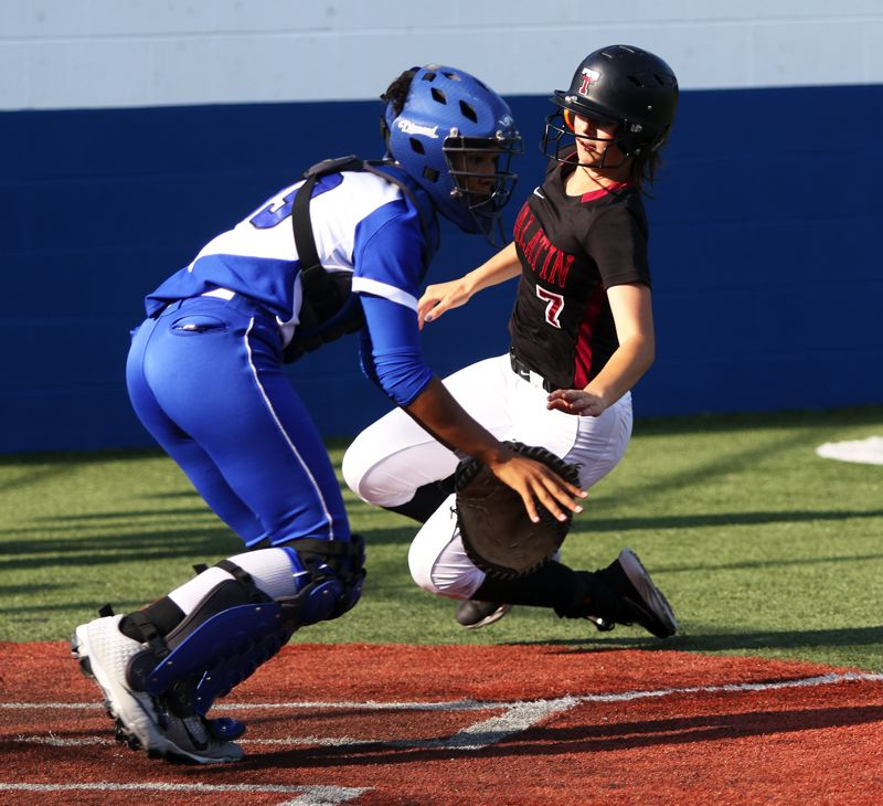 PMG PHOTO: DAN BROOD - Tualatin junior Savannah Braun (right) slides to home plate as Grants Pass catcher Toni Stevens awaits the ball during the sixth inning of the Wolves' 10-7 win on Tuesday.