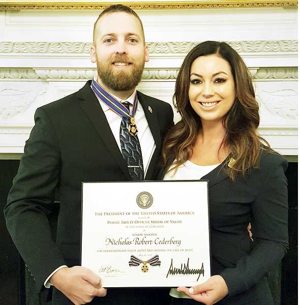 SUBMITTED PHOTO  - Nic and Hayley Cederberg display the National Public Safety Officer Medal of Valor and certificate he received from President Donald Trump during a ceremony May 22 at the White House.