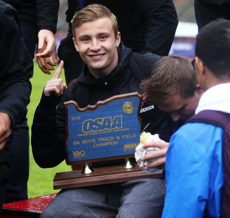 PMG PHOTO: DAN BROOD - Tualatin High School senior Jake Anderson holds the Class 6A state championship trophy.
