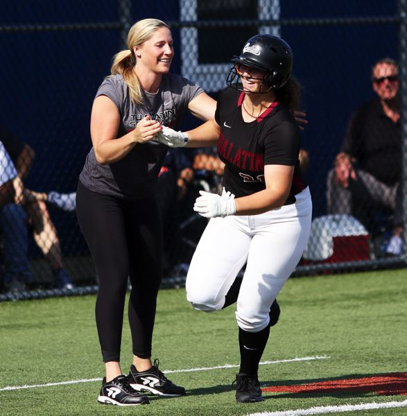 PMG PHOTO: DAN BROOD - Tualatin High School senior Emily Johansen is congratulated by Timberwolf coach Jenna Wilson after hitting a third-inning home run.