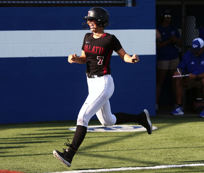 PMG PHOTO: DAN BROOD - Tualatin High School junior Savannah Braun smiles as she circles the bases following her seventh-inning grand slam in Tuesday's state playoff semifinal game in Grants Pass.