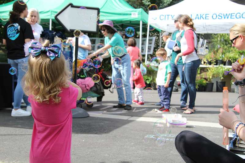 PMG PHOTOS: SAM STITES - Lake Oswego Public Library Volunteers blew bubbles for the small children to chase the D Avenue Block Party hosted by the City of Lake Oswego.