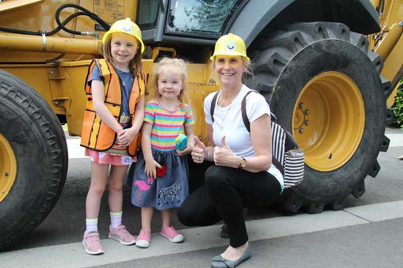 PMG PHOTO: SAM STITES - Deborah Chapman (right) poses with her granddaughters Penelope (left) and Fiona (center) at the D Avenue Block Party.
