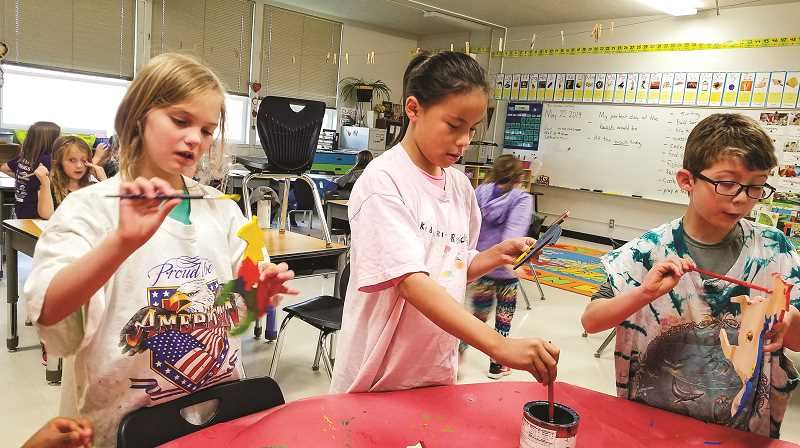 PHOTO COURTESY OF KAREN BRYANT  - Crooked River Elementary second-grade students Jessica Mapes, left, Khasidy Left Hand and Luam Griffin paint their wooden mustang figures during a class art lesson.