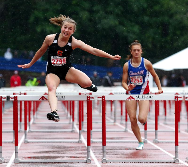 PMG PHOTO: JONATHAN HOUSE - Emma Jones, Scappoose hurdler, battles through a soggy 100 hurdles race en route to a fifth-place finish at state.