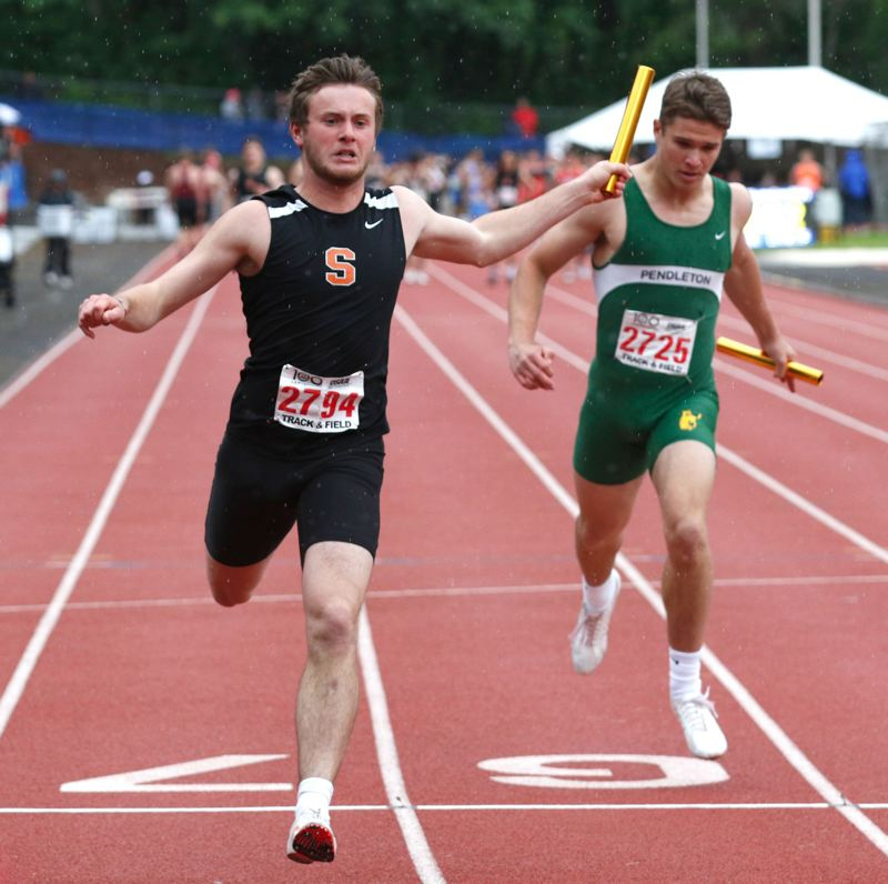 PMG PHOTO: JONATHAN HOUSE - Tyler Holcomb (left) caps the Scappoose boys' 4x100 relay run at state with a season-best time that earns fourth place.