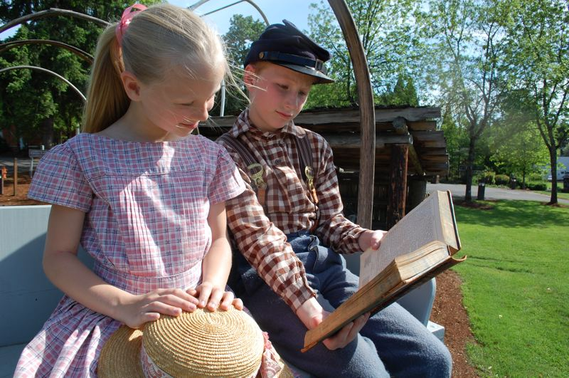 PMG PHOTO: RAYMOND RENDLEMAN - Penelope Rice and Callan Geer, who will participate in the Portland Rose Festival's Grand Floral Parade, read 19th-century tales at the End of the Oregon Trail Interpretive Center in Oregon City.