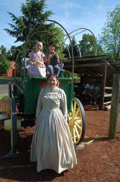 PMG PHOTO: RAYMOND RENDLEMAN - Cheryl Rice, along with grandchildren Penelope Rice and Callan Geer, stands in front of one of the wagons that people used to travel 2,000 miles to Oregon City in the 1840s.