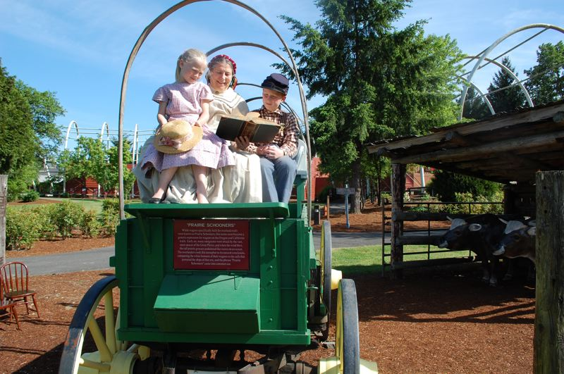 PMG PHOTO: RAYMOND RENDLEMAN - Cheryl Rice, along with grandchildren Penelope Rice and Callan Geer, read 19th-century tales at the End of the Oregon Trail Interpretive Center in Oregon City to prepare for participation in the Portland Rose Festival's Grand Floral Parade.