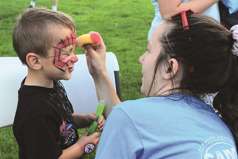 HOLLY SCHOLZ/CENTRAL OREGONIAN  - Crook County Health Department Prevention Coordinator Heather Stuart paints Spider-Man on 4-year-old William Morin.