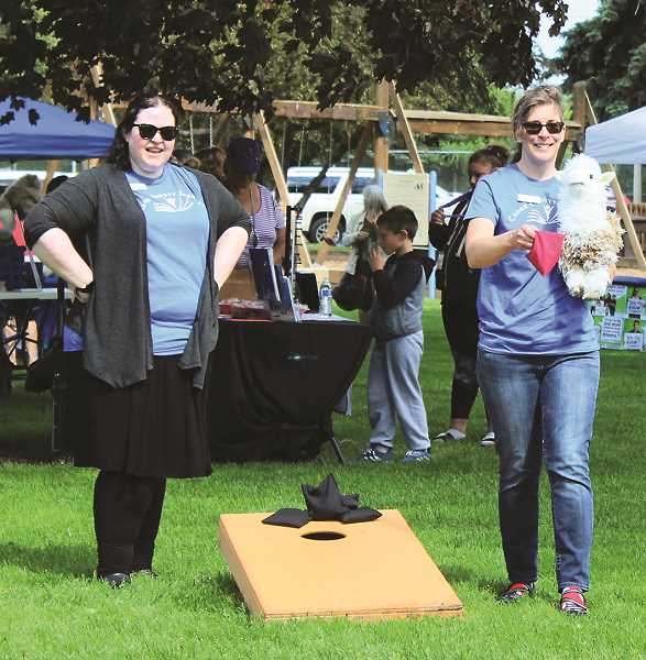 ROOK COUNTY HEALTH DEPARTMENT PREVENTION HOLLY SCHOLZ/CENTRAL OREGONIAN  - Crook County Library Teen Services Librarian Heather Jones, left, and Children's Services Librarian Specialist Jennifer Fischer competed in the bag toss tournament with the help of a llama puppet.